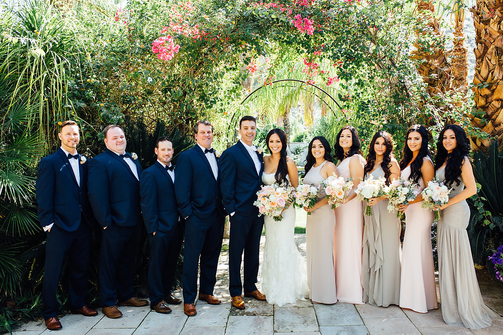 bridal party under bougainvillea arch